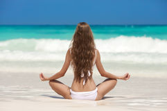 Kvinnameditation på den tropiska stranden Arkivbilder