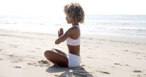 Kvinnameditation på stranden arkivfilmer