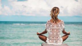 Kvinnameditationen i en yoga poserar på stranden royaltyfria bilder