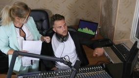 Kvinnamentorn med dokument i hand och mannen i hörlurar near mikrofonen på studion stock video