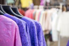 Kvinnamodebegrepp, färgrik kvinnaskjorta som hänger i shoppa Fotografering för Bildbyråer
