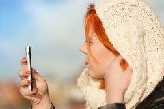 Kvinnamodeflicka med den utomhus- smartphonen Arkivbilder