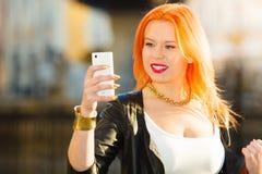 Kvinnamodeflicka med den utomhus- smartphonen Royaltyfri Bild