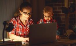 Kvinnamoder som arbetar med en behandla som ett barn som är hemmastadd bak en dator Arkivfoton