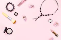 Kvinnamodetillbehör, smycken och skönhetsmedel på rosa bakgrund Lekmanna- lägenhet royaltyfria bilder