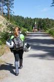 Kvinnamotorcyklisthandelsresande som kommer till dragningen och gör bilden med hennes smartphone Arkivbilder