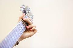 Kvinnamusiker som rymmer en gitarr som spelar ett G-ackord Arkivfoton