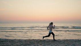 Kvinnan är att köra som är snabbt längs havskust på stranden på solnedgången i ultrarapid arkivfilmer