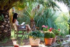 Kvinnan är avslappnande i en härlig trädgård Royaltyfri Foto