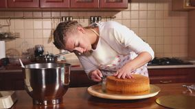 Kvinnan är den bitande bakade preformen för kaka på en roterande platta i kök arkivfilmer