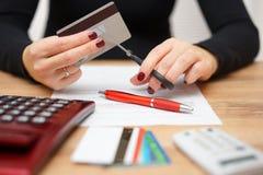 Kvinnan är den bitande kreditkorten, eller kontokortet med sax över lurar arkivbilder