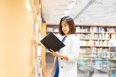 Kvinnan är finna och läsa en bok i bokhandeln royaltyfri fotografi