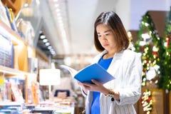Kvinnan är finna och läsa en bok i bokhandeln arkivbild