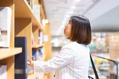Kvinnan är finna och läsa en bok i bokhandeln royaltyfri foto