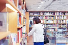 Kvinnan är finna och läsa en bok i bokhandeln fotografering för bildbyråer