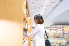 Kvinnan är finna och läsa en bok i bokhandeln royaltyfria bilder