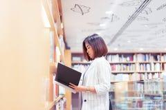 Kvinnan är finna och läsa en bok i bokhandeln arkivfoton