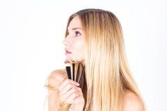 Kvinnan är hållande kosmetiska borstar Smink Arkivbild