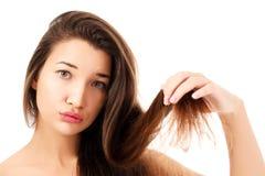 Kvinnan är inte lycklig med hennes bräckliga hår Arkivbild
