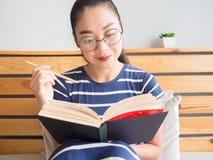 Kvinnan är läseboken på sängen royaltyfri foto