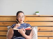 Kvinnan är läseboken på sängen arkivbilder