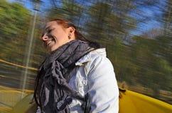 Kvinnan är lycklig att rida en karusell royaltyfri foto