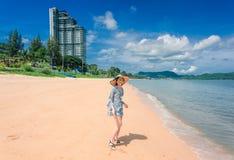 Kvinnan är lycklig och strosar på en strandsemester fotografering för bildbyråer