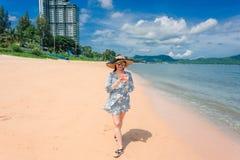 Kvinnan är lycklig och strosar på en strandsemester arkivfoto