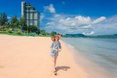 Kvinnan är lycklig och strosar på en strandsemester royaltyfri foto