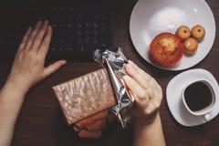 Kvinnan äter choklad och söt mat på arbetsplatsen Fotografering för Bildbyråer