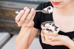 Kvinnan äter efterrätten med blåbär i restaurang Arkivbilder