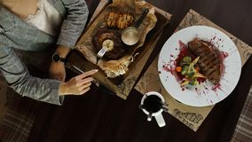Kvinnan äter en sund mat i en restaurang på trätabellen Äta lunch avbrottet Top beskådar royaltyfri foto