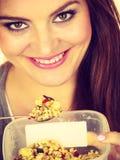 Kvinnan äter havremjölet med torra frukter banta arkivbild