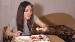Kvinnan äter rullar som levereras till huset Japansk mat stock video