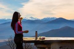 Kvinnan äter smörgåsar och dricker te mot landskap med berg royaltyfri bild
