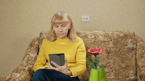 Kvinnan åldrades att vila hemma på soffan för minnestavlaPC:N Hon bläddrar igenom sidorna och läste försiktigt Feriehem stock video