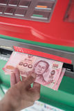 Kvinnan återtar kassa från ATM royaltyfria bilder