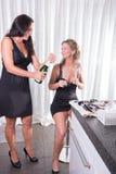 Kvinnan öppnar en flaska av champagne Royaltyfri Foto