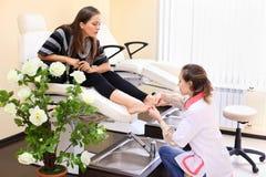 Kvinnan öva chiropody som tar omsorg av fot Royaltyfria Foton