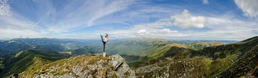 Kvinnan öva yoga på en bergöverkant, Carpathian berg fotografering för bildbyråer