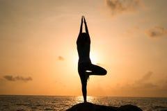 Kvinnan öva yoga på gryning, det finns en asana på en sten, gryning och en bild av flickan, att tycka om gryning, för att vara ly arkivfoton