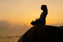 Kvinnan öva yoga på gryning, det finns en asana på en sten, gryning och en bild av flickan, att tycka om gryning, för att vara ly royaltyfri fotografi