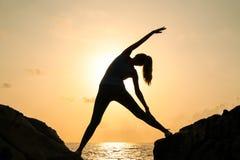 Kvinnan öva yoga på gryning, det finns en asana på en sten, gryning och en bild av flickan, att tycka om gryning, för att vara ly arkivbild