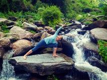 Kvinnan öva yogaasanaen Utthita Parsvakonasana utomhus arkivfoton