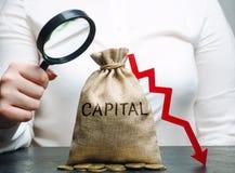 Kvinnan analyserar data på kostnaden av huvudstad i företaget huvudutflöde Unprofitable aktivitet av företaget Låg huvudstad royaltyfri foto
