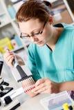 Kvinnan analyserar genetiska koden Arkivfoton