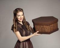 Kvinnan annonserar den närvarande gåvaasken för kakan, Retro flicka som mat levererar royaltyfri fotografi