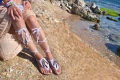 Kvinnan annonserar grekiska sandaler och smycken på stranden arkivfoton