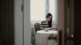 Kvinnan använder bärbara datorn och att tycka om morgonkaffe på ljust äta middag glidare till det vänstert, sikt till och med de  lager videofilmer