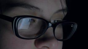 Kvinnan använder en minnestavla på natten skärmen av som reflekteras på exponeringsglasen arkivfilmer